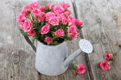 bouquet-roses-watering-can-wooden-background-51316059