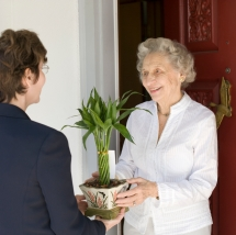 Attractive senior woman receiving gift of bamboo plant at front door